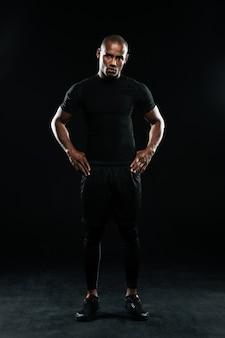Homem sério de esportes afro-americanos, em pé com os braços nos quadris