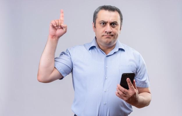 Homem sério de meia-idade usando camisa listrada azul, proibindo algo levantando o dedo indicador e segurando o telefone celular com a outra mão em um fundo branco