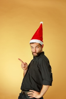 Homem sério de natal com chapéu de papai noel no estúdio laranja apontando para a esquerda