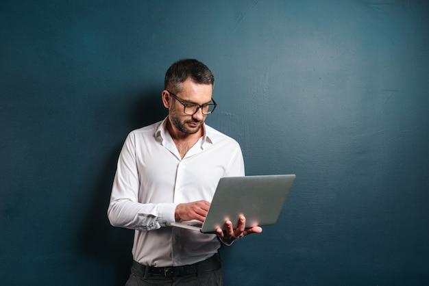 Homem sério de óculos usando o computador portátil.
