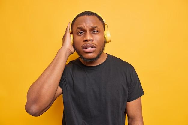 Homem sério de pele escura e barbudo ouvindo uma transmissão e segurando fones de ouvido estéreo