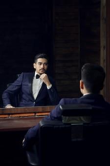 Homem sério de terno azul e borboleta sentado na cadeira, olhando no espelho na barbearia.