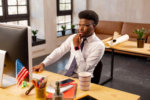 Homem sério e atencioso checando as informações enquanto olha para a tela do laptop