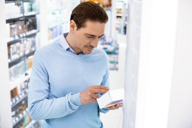 Homem sério e atencioso em uma farmácia segurando um remédio, lendo as instruções de uso