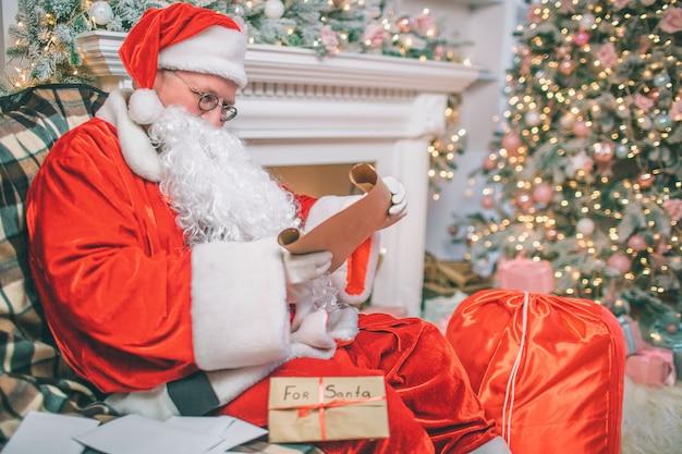 Homem sério e atencioso na suíte de natal senta e lê cartas. há outros além dele na mesa. homem senta-se na lareira e árvore de natal.