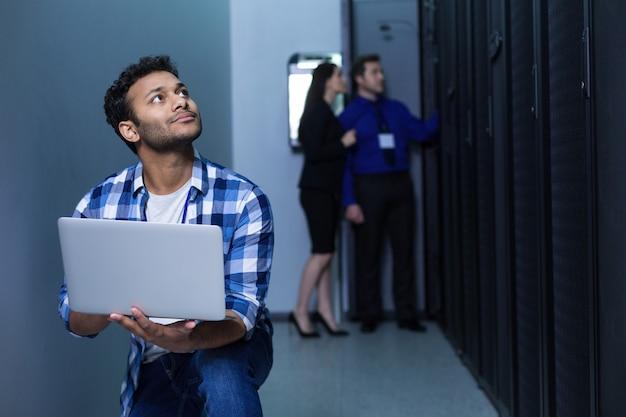 Homem sério e atencioso segurando um laptop e olhando para cima enquanto está sentado sobre um joelho