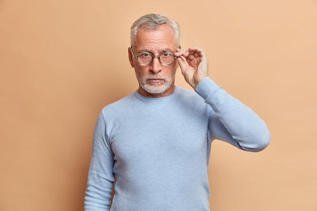 Homem sério e autoconfiante com barba grisalha mantém as mãos nos óculos olha diretamente para a frente, vestido com jumper casual, lista as informações cuidadosamente posa contra a parede bege
