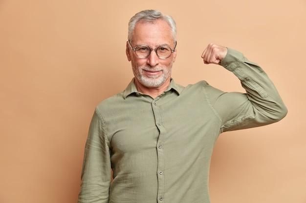 Homem sério e autoconfiante levanta o braço e mostra os músculos confiantes em sua força usando poses formais de camisa contra a parede marrom