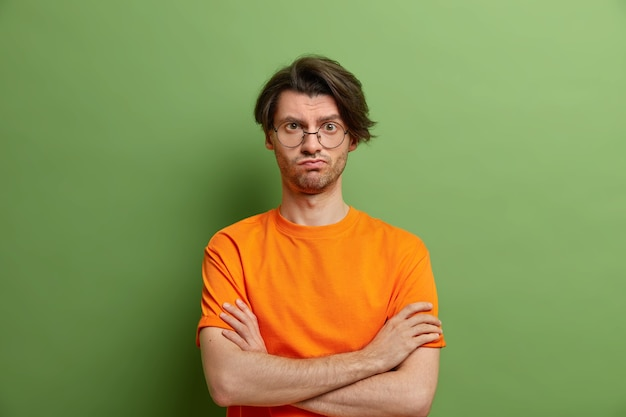 Homem sério e bonito de óculos com penteado da moda fica em pose assertiva e mantém os braços cruzados