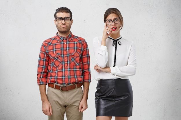 Homem sério e carrancudo com óculos grandes e lentes grossas, usa roupas formais e uma linda mulher intrigada com lábios vermelhos
