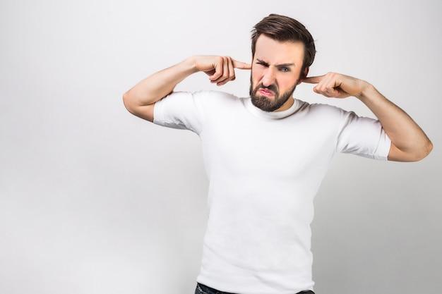 Homem sério e com raiva que não quer ouvir nada. ele está fechando os ouvidos com os dedos. isolado na parede branca