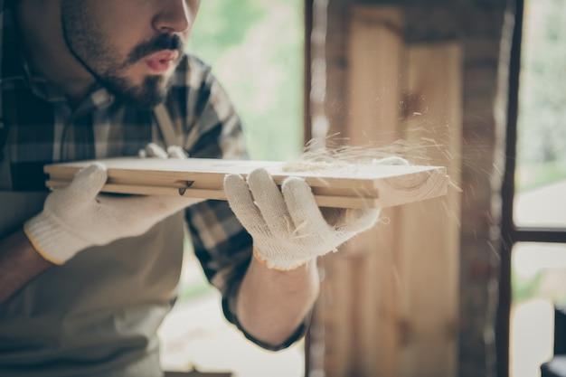 Homem sério e confiante colhido soprando serragem de um bloco de madeira antes de polir