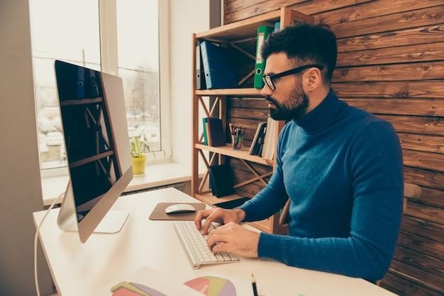 Homem sério e confiante trabalhando no escritório, no computador e digitando