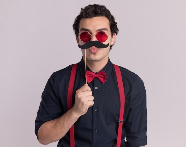 Homem sério e elegante com gravata borboleta usando óculos e suspensórios olhando para frente segurando bigode em um palito em pé sobre uma parede branca