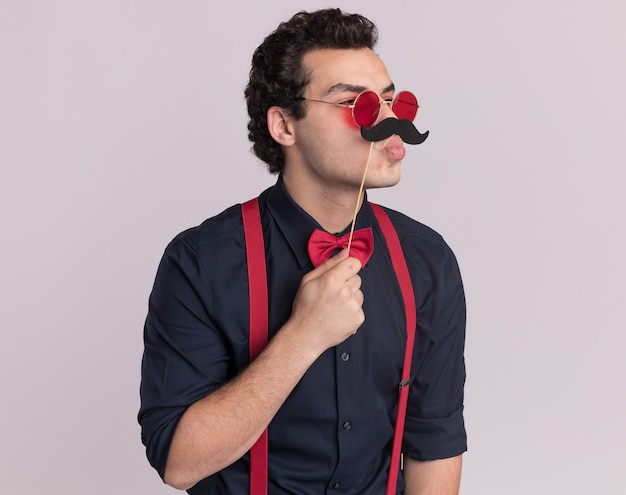 Homem sério e elegante com gravata borboleta usando óculos e suspensórios olhando para o lado segurando bigode em um palito em pé sobre uma parede branca