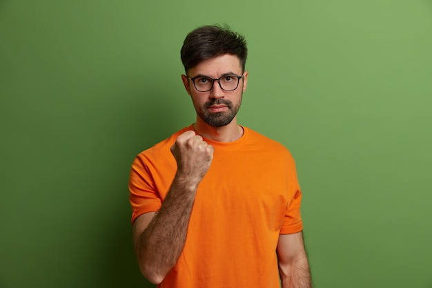 Homem sério e indignado sacode o punho, promete vingança, diz que vou te mostrar, avisa sobre alguma coisa, olha através dos óculos, veste camiseta laranja, expressa emoções negativas, isolado na parede verde