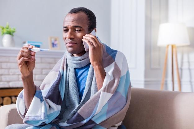 Homem sério e infeliz olhando para o termômetro e ligando para o hospital enquanto está com febre