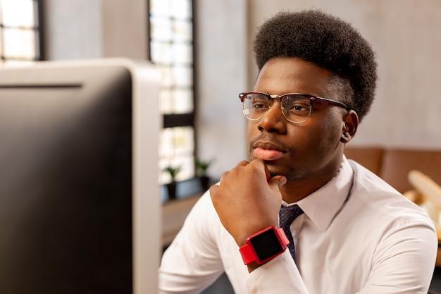 Homem sério e inteligente tocando seu queixo enquanto olha para a tela do computador
