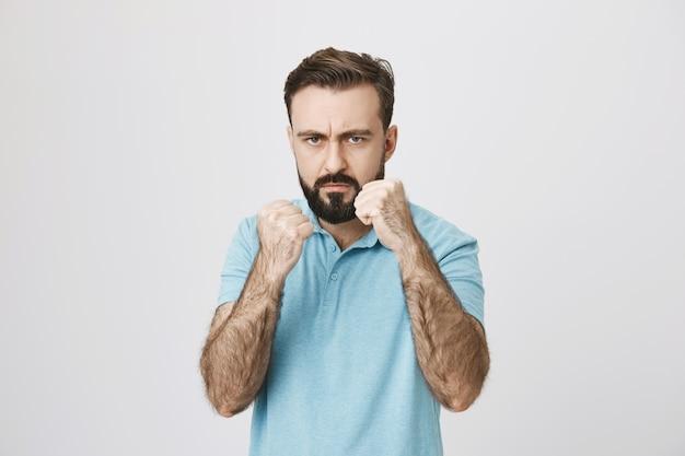 Homem sério e irritado levantando os punhos para lutar