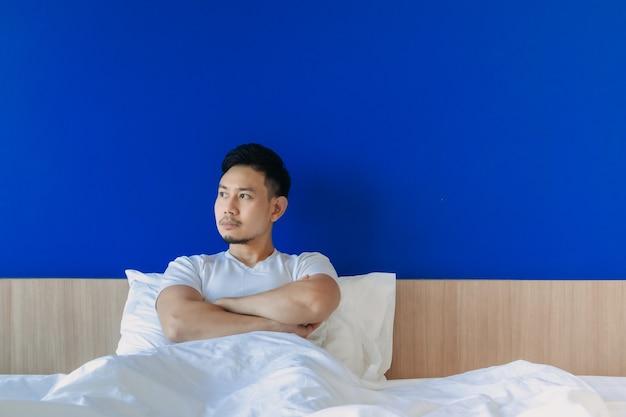 Homem sério e mal-humorado acorda na cama no fundo do espaço azul