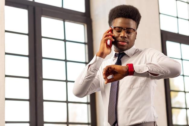 Homem sério e ocupado olhando as horas enquanto fala ao telefone
