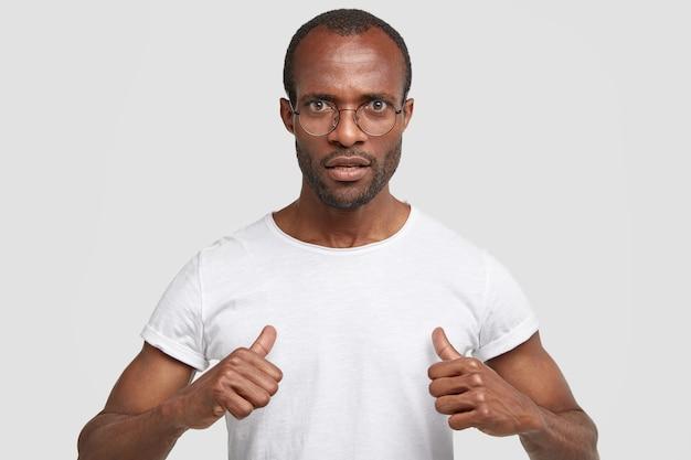Homem sério e rabugento aponta para si mesmo, surpreso por ter muitos deveres, usa uma camiseta branca casual, isolado na parede do estúdio