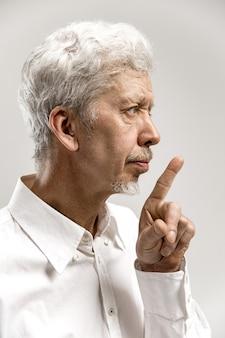 Homem sério e sênior assustado mantém o dedo da frente nos lábios, tenta manter a conspiração