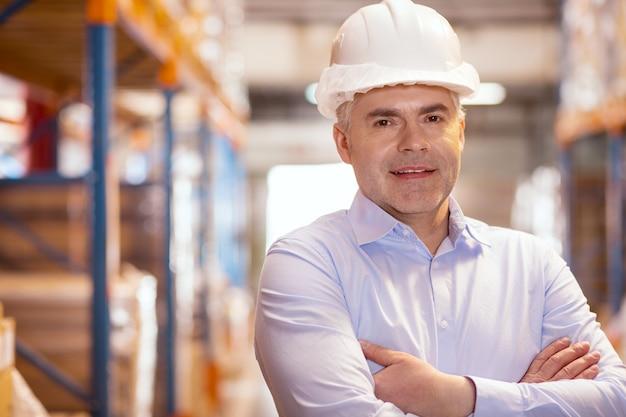Homem sério e simpático olhando para você enquanto trabalhava no depósito