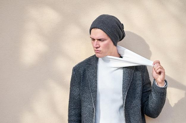 Homem sério elegante hippie vestindo um casaco cinza da moda puxando o suéter branco de lado.