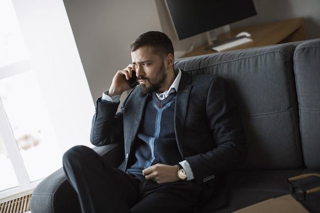 Homem sério em falar no smartphone