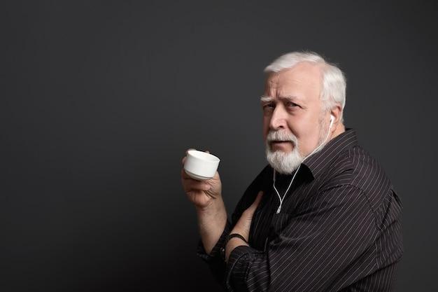 Homem sério em fones de ouvido e com um copo na mão