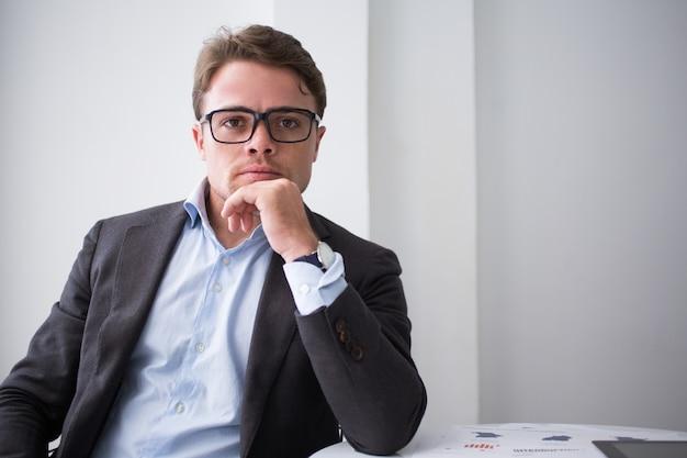Homem sério em óculos confiante em si mesmo