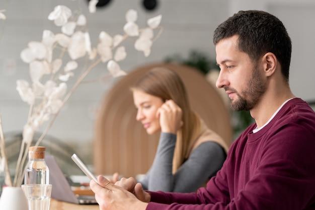 Homem sério em roupa casual rolando no touchpad enquanto está sentado no café com uma jovem