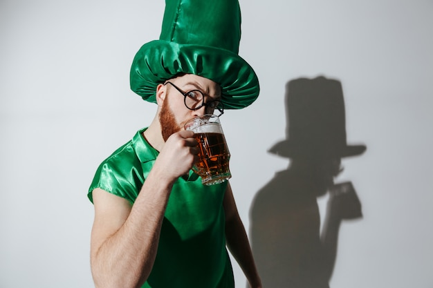 Homem sério em traje de st.patriks, bebendo cerveja