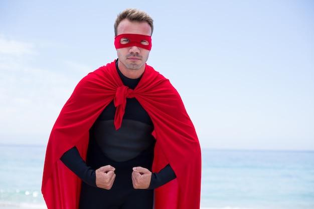 Homem sério em traje de super-heróis em pé na beira-mar