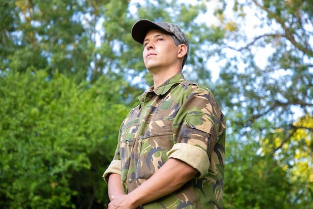 Homem sério em uniforme de camuflagem militar em pé no parque, olhando para longe.