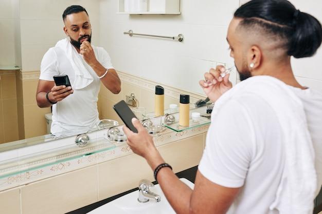 Homem sério, escovando os dentes no banheiro e lendo notícias na tela do smartphone