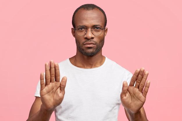 Homem sério faz um gesto de pare, rejeita algo, fica de pé contra uma parede rosa
