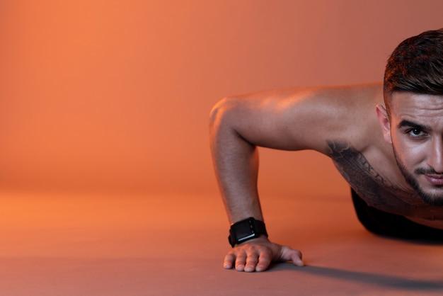 Homem sério fazendo flexões