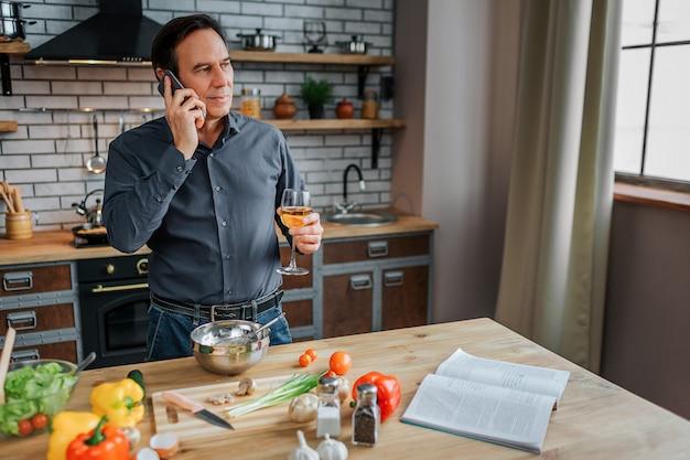 Homem sério ficar na cozinha à mesa. ele fala ao telefone e pensa. livro de receitas aberto e legumes deitado na mesa.