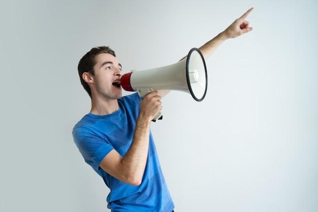 Homem sério, gritando no megafone e apontando para fora