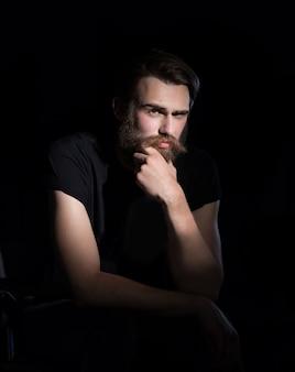Homem sério hipster sentado em uma cadeira. isolado em fundo preto