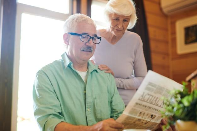 Homem sério lendo notícias recentes para sua esposa pela manhã enquanto está sentado à mesa em sua casa de campo