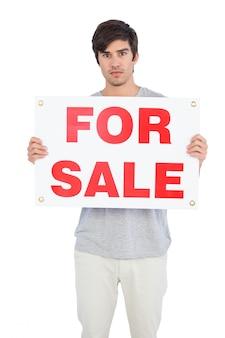 Homem sério, mostrando para a placa de venda