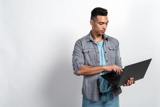 Homem sério mulato segurando um laptop nas mãos