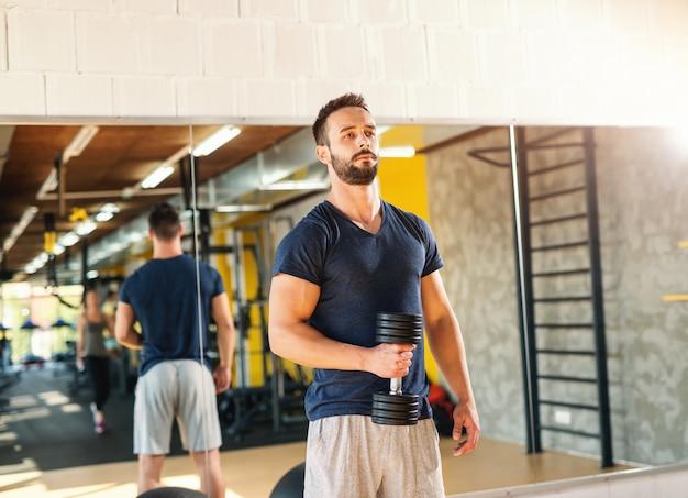 Homem sério musculoso no sportswear segurando halteres. no fundo, seu reflexo no espelho.