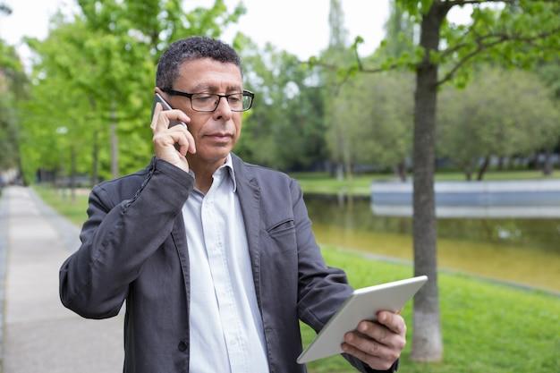 Homem sério, navegando em tablet e falando no telefone no parque