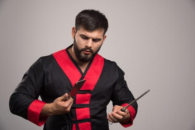 Homem sério olhando na chave de fenda e na faca.
