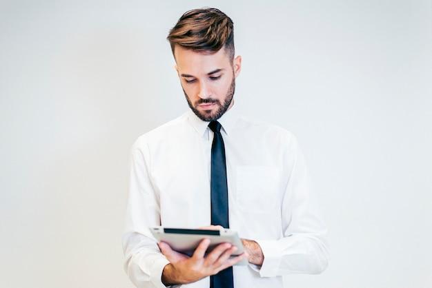 Homem sério olhando para um tablet