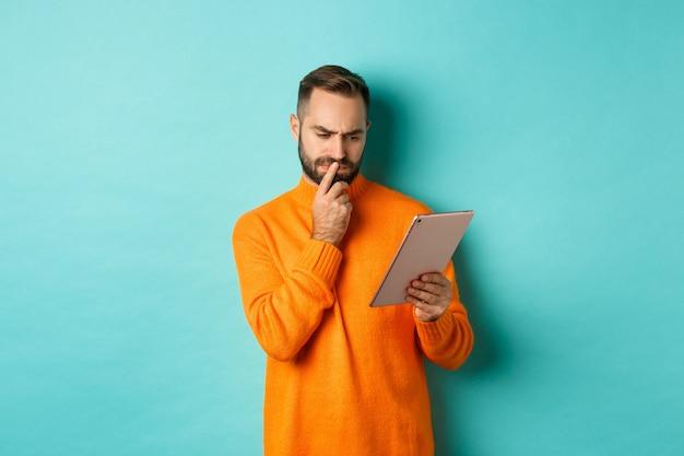 Homem sério pensando e olhando para a tela do tablet digital, lendo redes sociais,